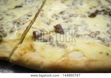 Large slices of Philly cheesesteak pizza served NY style