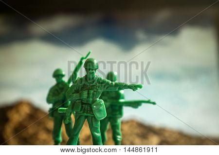 Green toy soldiers with mountaintops the lookout points the way