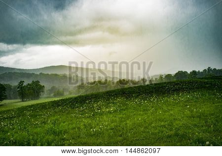 Moody stormy landscape field with mountains in background summer