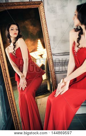 Black haired woman in red evening gown seated before full length mirror looking at reflection.
