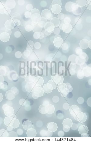 A blue grey bright sparkly abstract background of retro tinted Christmas holiday bokeh lights. Shallow depth of field.