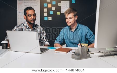 Two designers collaborating on a project together in front of a laptop computer while working in an office