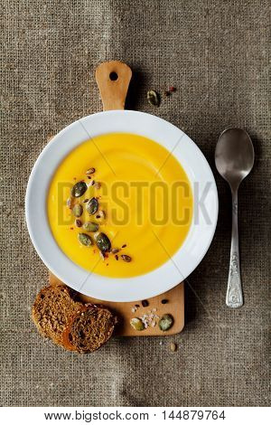 Pumpkin soup with rye bread in white bowl. Dietary vegetable and healthy food. Rustic style. Top view, flat lay.