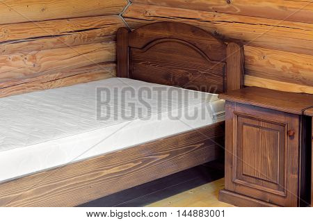 wooden corner of room with a wooden bed and nightstand