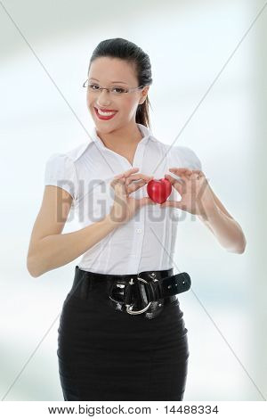 Young business woman holding heart shaped toy