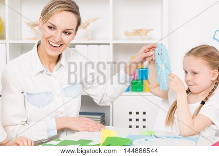 Smiling pre-school teacher admiring a paper napkin made by a little girl sitting beside