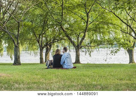 Washington, DC., USA - August 4, 2016: Romantic couple having a picnic by the Potomac River in the city surrounded by willow trees