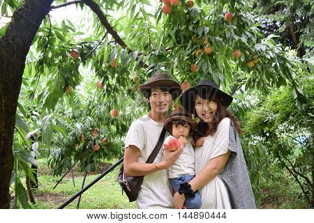 Young Family Is Smiling At Peach Orchard