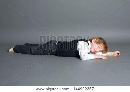 photo of little funny boy lying on dark background