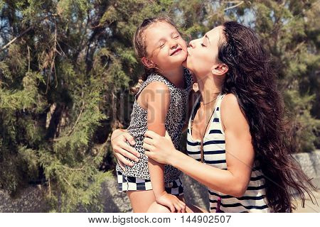 Happy mother kissing her fun enjoying daughter on summer geen background