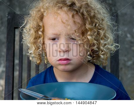 a  blond boy refusing to eat outside