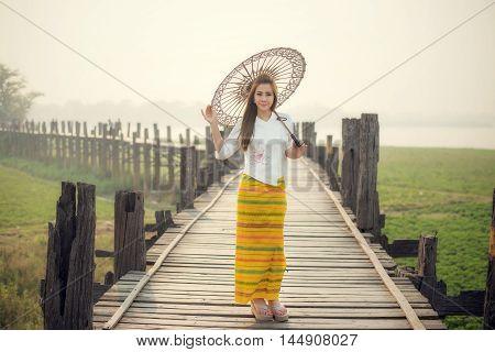 The Beautiful Burmese Woman In Myanmar Traditional Costume,with Umbrella Walking On Ubein Bridge, Ma