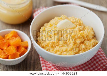 Millet porridge with baked pumpkin and butter in bowl on wooden table. Baby food.