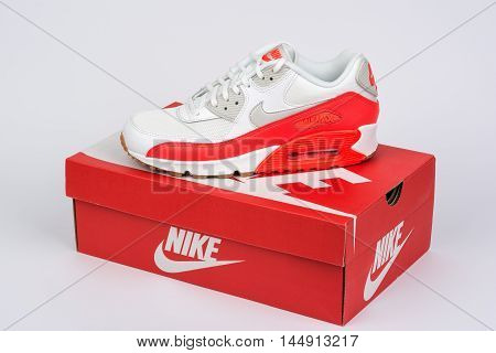 BURGAS BULGARIA - AUGUST 30 2016: Nike Air MAX lady's - women's shoes - sneakers - trainers in white and orange illustrative editorial over Nike shoes box on white background