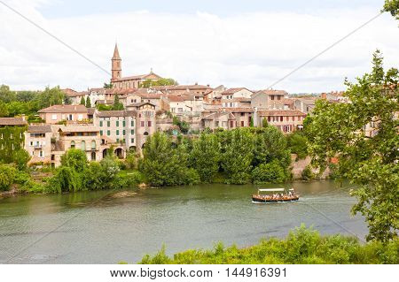 Boat Sailing In Tarn River With The View Of Albi Behind, France