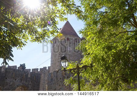 tower of carcassonne city and a lamppost and the sun
