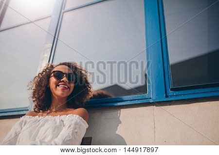 Shot of happy young african woman sitting outdoors looking away and smiling. Female wearing sunglasses sitting outside looking happy.