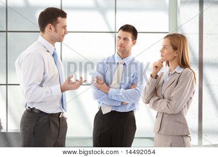 Lavoratori giovani attraenti ufficio casual parlando nel corridoio.?
