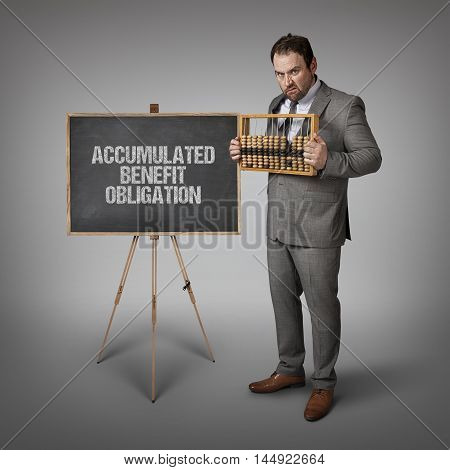 Accumulated Benefit Obligation text on blackboard with businessman and abacus