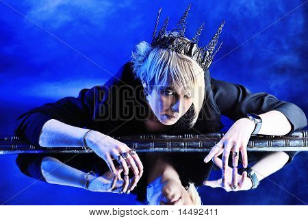 Portrait of an artistic young man in a king costume. Studio shot.