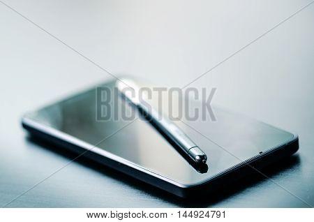 Stylus pen on a mobile. Technology background. Dark background.