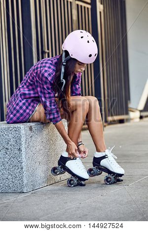 Beautiful young woman put on roller skates and tying shoelaces. Girl is going rollerblading. Sitting on a grey bench putting on skates. Sport lifestyle.