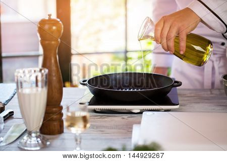 Liquid pours onto frying pan. Male hand holding a bottle. Portable electric cooker. Chef's work in the morning.