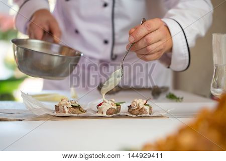 Hands with saucepan and spoon. Brown pieces of meat. Roquefort sauce for medallions. Taste the masterpiece.