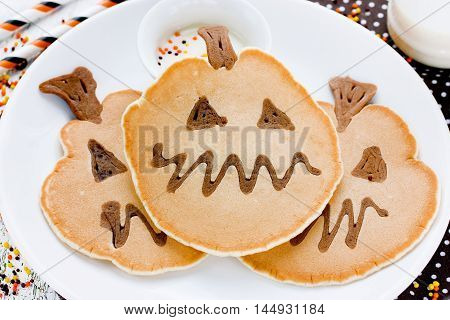 Fun pumpkin pancakes for Halloween holiday party. Yummy pumpkin pancakes shaped like a pumpkin selective focus