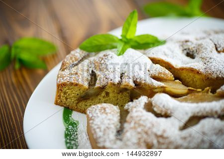 cake with pears in powdered sugar on a wooden table