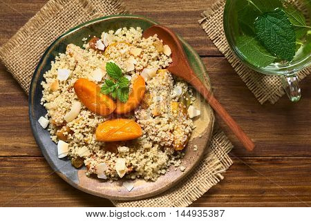 Couscous dessert with apricots yellow raisins coconut flakes and cinnamon garnished with lemon balm leaf fresh herbal tea on the side photographed overhead with natural light (Selective Focus Focus on the top of the dessert and the tea)