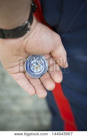 NEW YORK MAY 27 2016: A US Marine displays the US Fleet Forces Command coin received at the re-enlistment and promotion ceremony held at the National September 11 Memorial site during Fleet Week 2016.