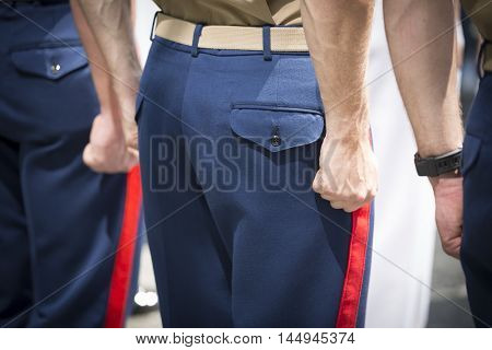 NEW YORK MAY 27 2016: Clenched fists of US Marine Corpsman standing at attention during the re-enlistment and promotion ceremony at the National September 11 Memorial site during Fleet Week 2016.