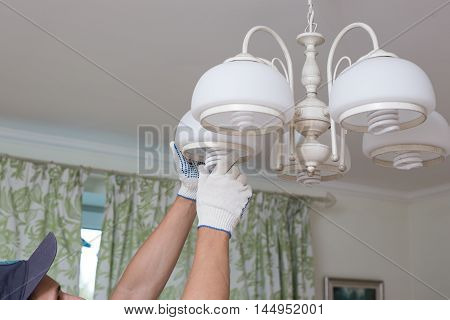 Man changes an electric light bulb, energy efficiency.