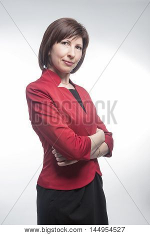 Business People Concepts and Ideas. Portrait of Confident Caucasian Business Brunette Woman Posing in Red Suit Against White. Vertical Orientation