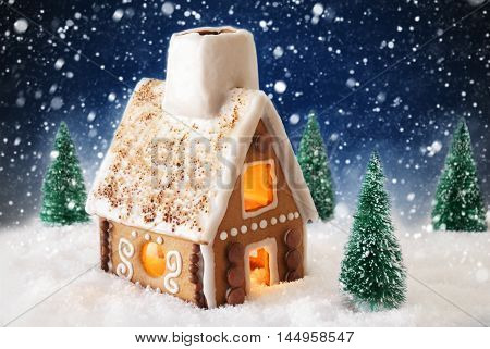 Gingerbread House In Snowy Scenery As Christmas Decoration. Christmas Trees And Candlelight For Romantic Atmosphere By Night. Dark Blue Background With Snowflakes. Christmas Card For Seasons Greetings