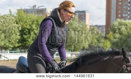 Girl riding a horse professionally engaged in the outdoors
