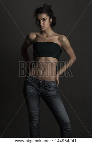 Female model sad face and dark skin and black hair and jeans and black top with nice body shape and middle east looking and dark background.
