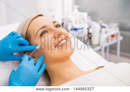 Beautiful woman gets beauty facial injections. Face aging injection. Aesthetic Cosmetology poster