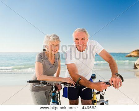 Ehemaliger Paar mit ihren Fahrrädern am Strand