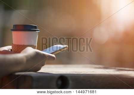 Woman outdoors holding smart phone in morning sunlight