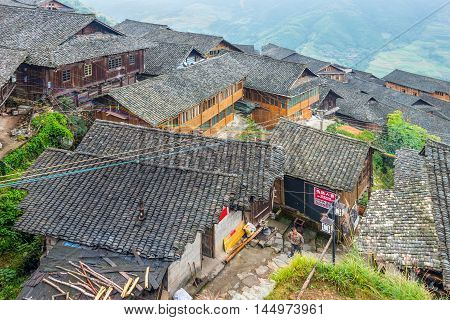 Longsheng China - October 19 2013: Traditional chinese Long Ji minority village wooden houses in cloudy weather. There are two Zhuang ethnic group villages live in the mountain - Ping An Village and Long Ji village at Longsheng Guangxi province China.