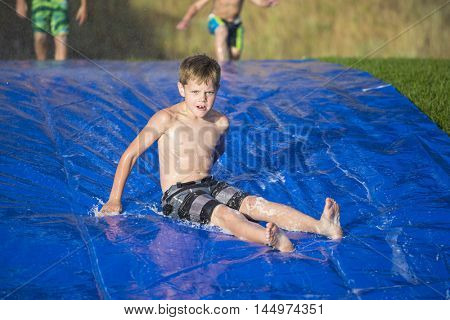 Young boy sliding down a slip and slide outdoors