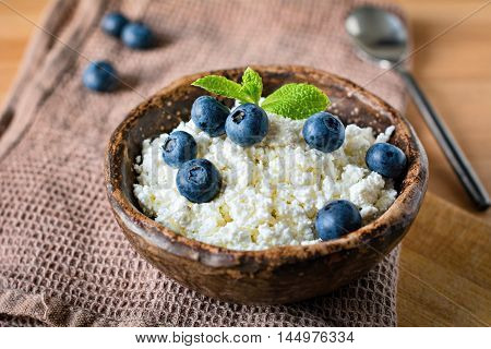 Farmers cheese, cottage cheese or quark - healthy homemade dairy product for breakfast. Topped with blueberries and mint leaf