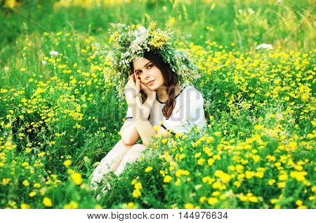 Beautiful Girl In Wreath Of Flowers  In Meadow On Sunny Day. Portrait Of Young Beautiful Woman Weari