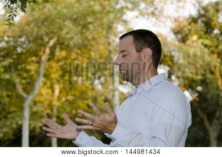 Man praying outdoors with his hands extended and open in praise.
