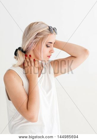 Beautiful sensitive woman touching her neck. Side view of young attractive blonde in sunglasses, white background