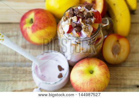 Slices of apple peach nectarine plum and banana blended with yogurt and chocolate corn flakes on wooden table top view