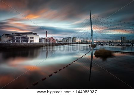 Sunrise and sweeping clouds at the River Tawe and the Millennium bridge in Swansea