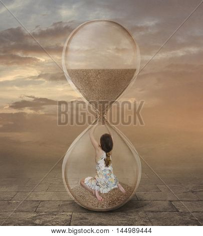 A girl is inside a hourglass. She tries to stop time.